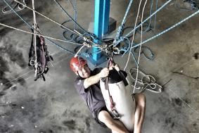 Rope access training student grabbing on a bag while training