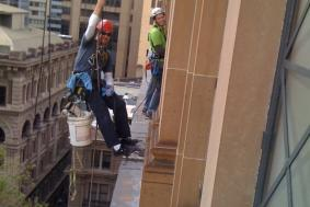 Two workers hanging on ropes outside of building to reach windows