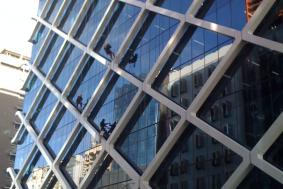 Workers hanging from outside of building to clean windows that are hard to reach