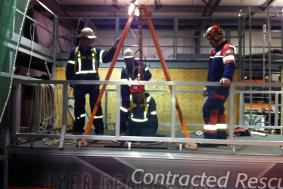 Three students observing technician being lowered in confined space for rope training