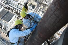 Two employees using rope access to reach high spot on pipeline refinery