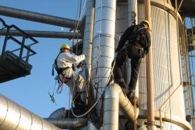Two workers in Oil & Gas industry using rope access to reach side of pipeline