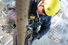 Employee in Oil & Gas industry using rope access at a pipeline refinery
