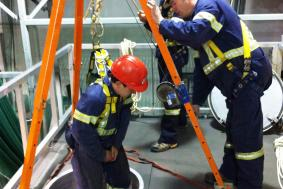 Student hanging from harness being lowered in a confined space