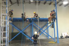 Five students on blue scaffold working on rope access training with technician observing