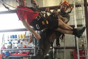 Two students practicing rope access training at training facility