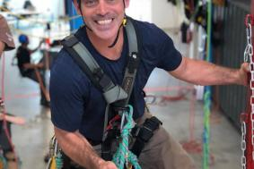 Student smiling to camera while rope training at practice facility