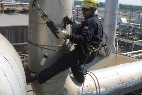 Employee in Oil & Gas industry using rope access at pipeline refinery to check measurements