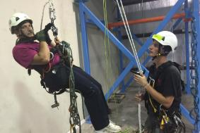 Technician in black shirt teaching student in maroon shirt rope access training