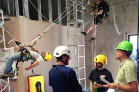 Trainee practicing rope access training by climbing with trainer