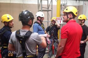 Workers are huddled together for rope access training