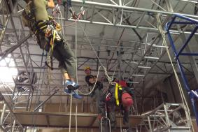 Student hanging from ceiling with ropes working on rope access training certification