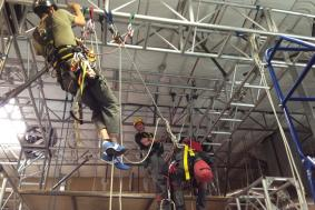 Student working with rope access technicians at a training facility