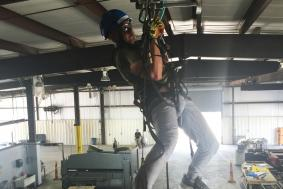 Student practicing rope access training and hanging from ceiling with ropes