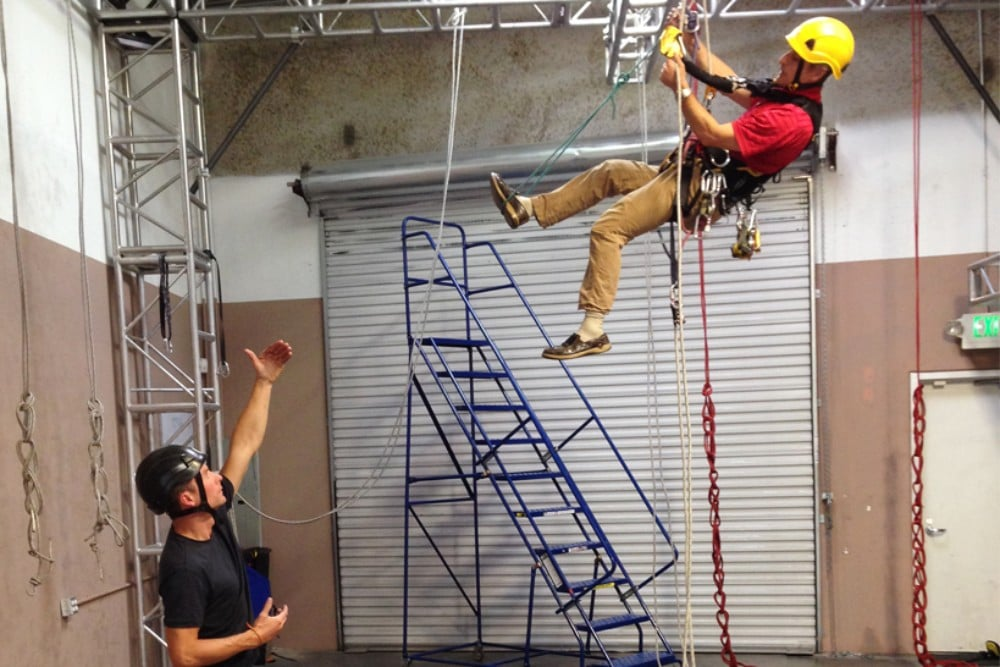 Rope access trainee with instructor in training facility
