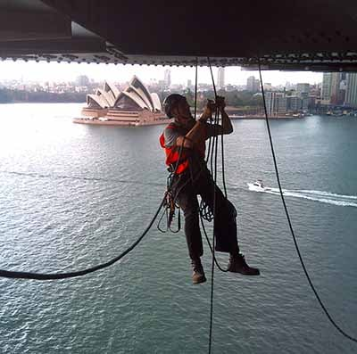 Rope access worker suspended under a bridge near the opera house in Sydney, Australia